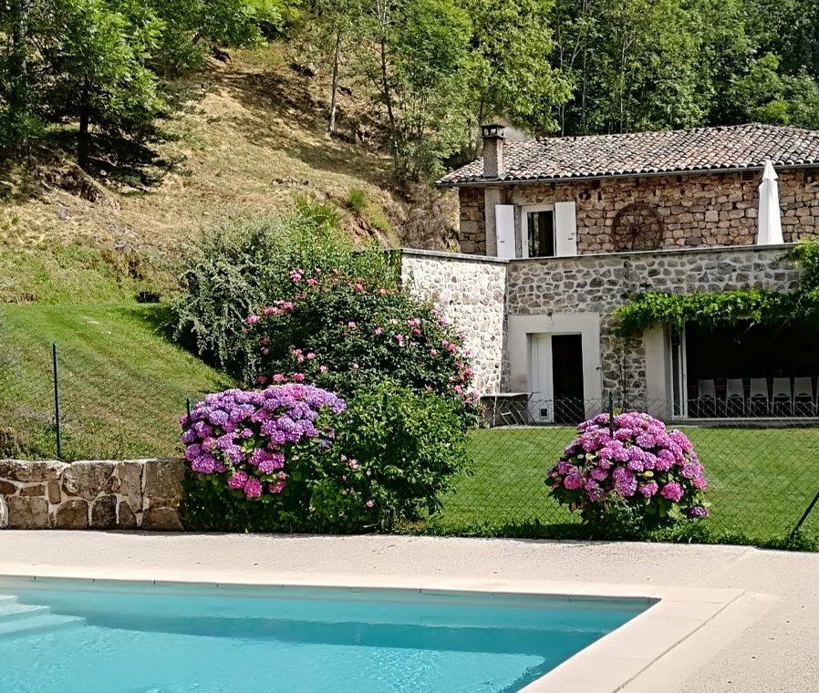 la parfaite présentation du grand gîte les Combes en Ardèche, la psicien chauffée, la pelouse pour les jeux et la maison ouverte sur l'extérieur